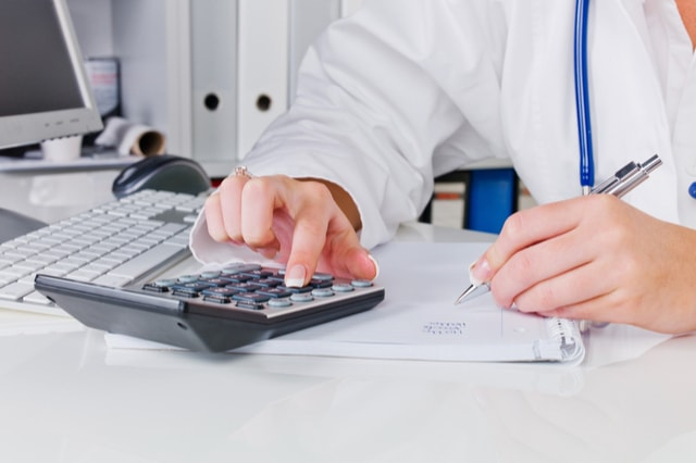 doctor calculates the costs of a surgery